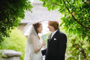 Bride & groom on their wedding day in the rain outside St Mary