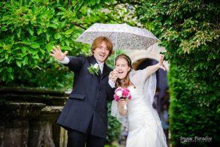Bride & groom under umbrella at St Mary