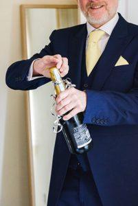 man opening champagne in celebration of Bristol zoo wedding