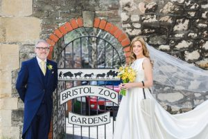 Father and bride pose next to the gates of Bristol zoo before the wedding ceremony