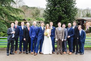 Groomsmen pose for picture with the bride and groom in the gardens of Bristol zoo