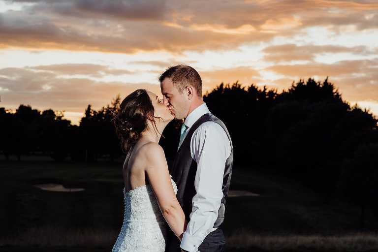 Kiss at sunset in the garden of Cotswold spa hotel wedding venue