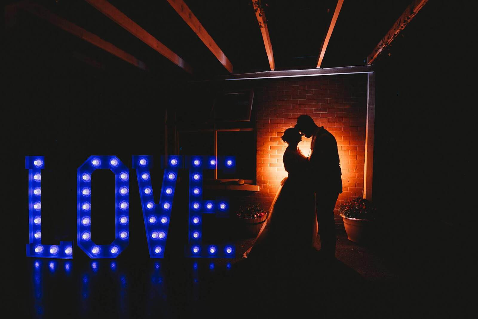 Bride & groom Silhouette with giant love letters night photo