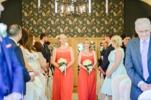 Bridesmaids walking down the aisle of the Hare and hounds wedding