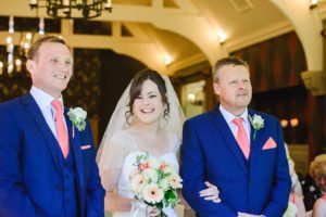 Bride smiling as her father gives her away to groom at their wedding ceremony at the Hare and hounds, Tetbury