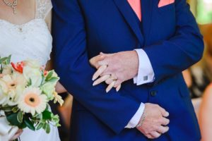 Father of the bride holds daughters hand before giving her away