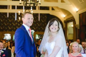 Bride and groom smiling during their wedding ceremony at the Hare and hounds Tetbury