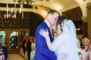 Bride and groom kiss after their wedding ceremony at the Hare and hounds