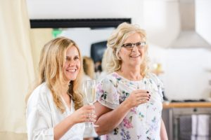 Bride with mum drinking champagne on wedding morning inside the Paintwork's apartments