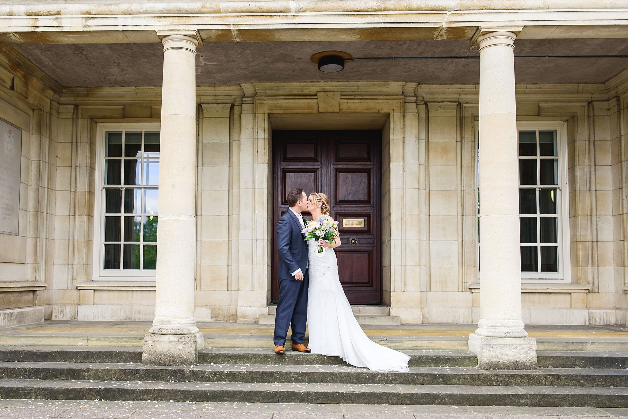 Couple kissing on the steps outside Trowbridge registry office on their wedding day