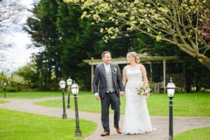 Couple walking in the garden of Leigh Park hotel on their wedding day