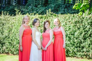 Three Bridesmaids and bride posing for a formal photo in the garden of the Hare and Hounds Tetbury