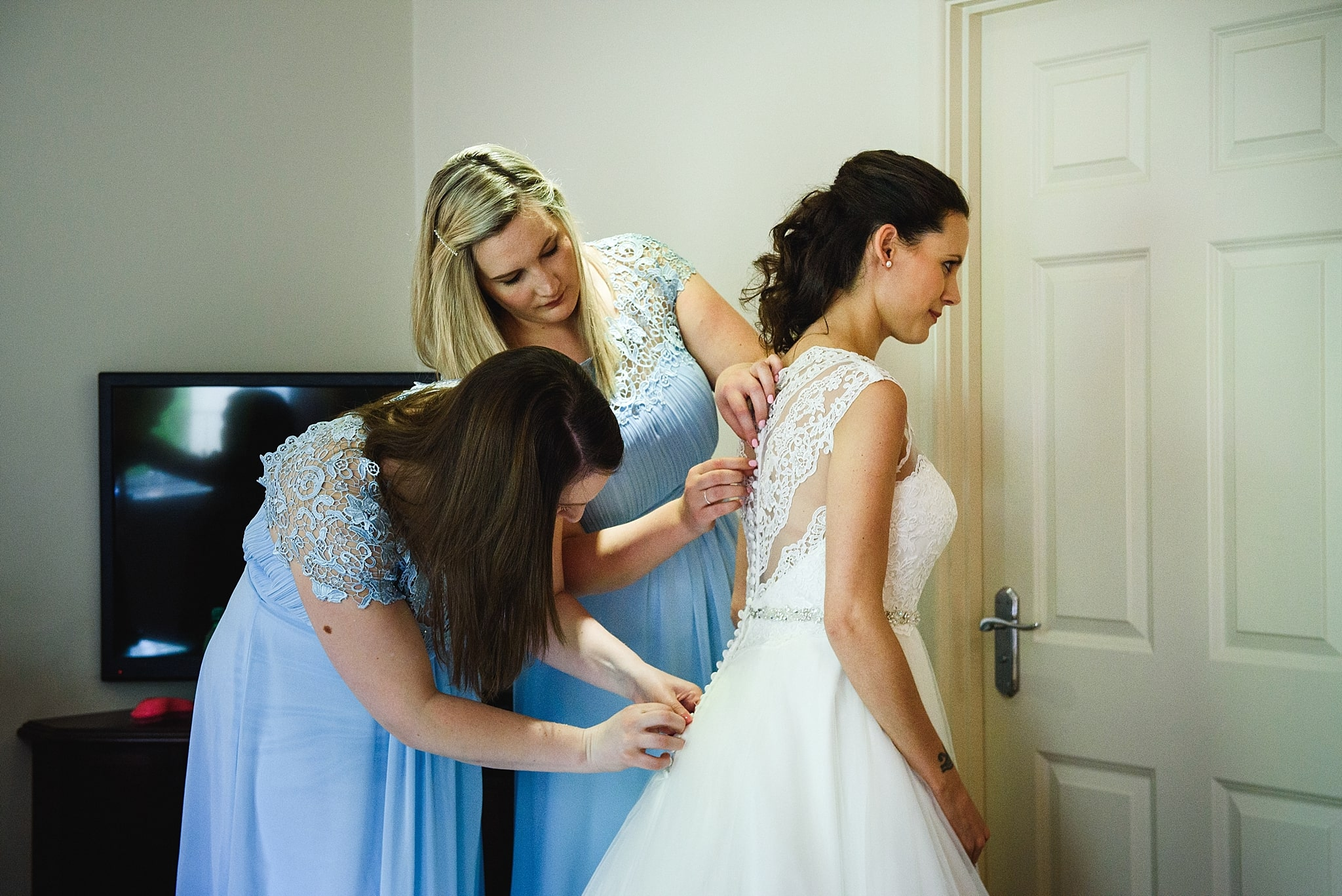 Bridesmaids help Bride put on her wedding dress
