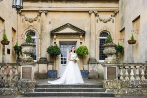 Bride stood on the steps in her wedding dress at Bailbook House