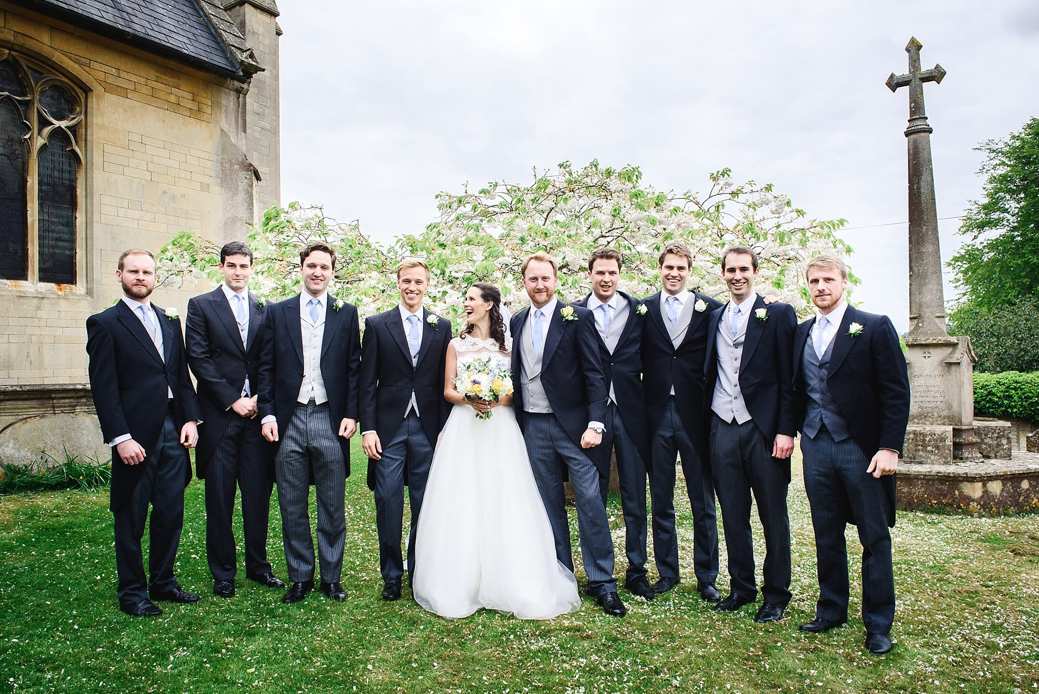 Groomsmen pose with bride outside St Swithins church, Bathford