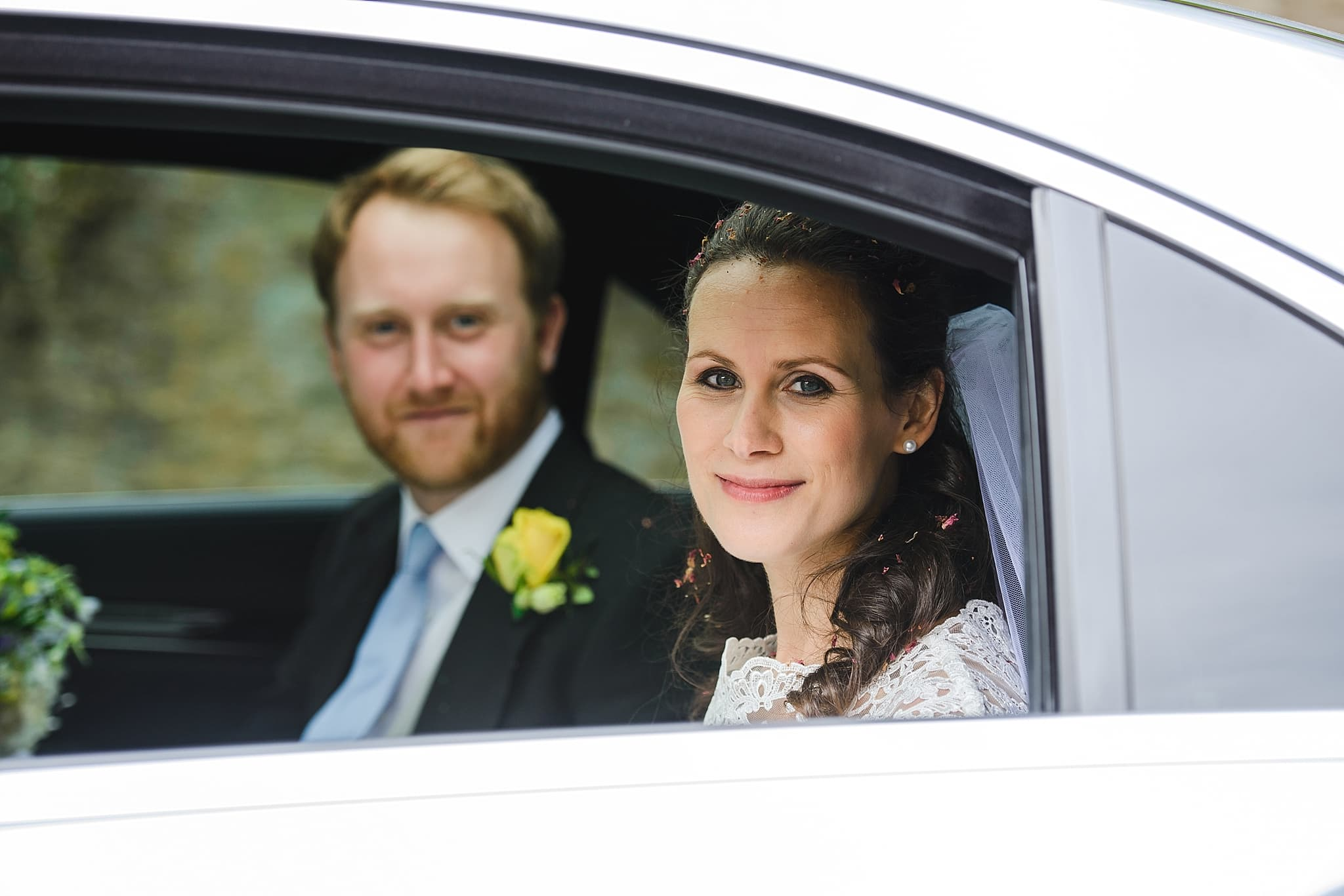 Bride and groom in wedding car on the way to Wick Farm wedding venue Bath