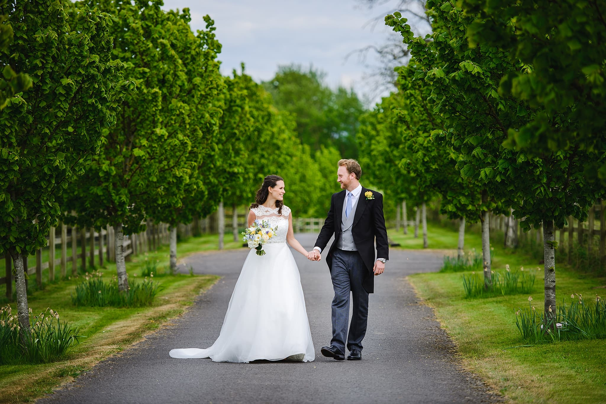 Bride and groom walk up the path of Wick Farm in Bath with trees either side of the path