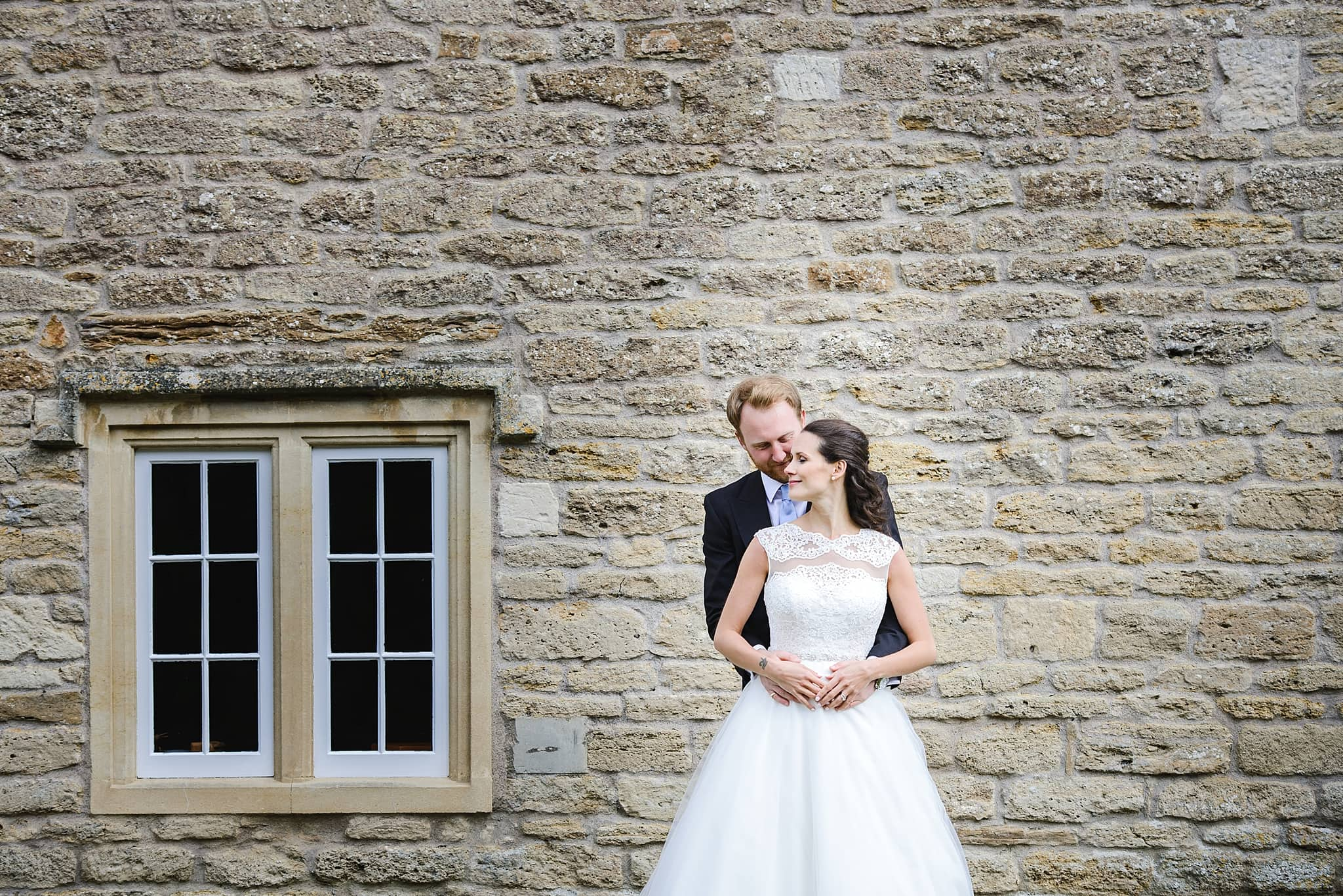 Bride and groom embrace each other in front of a brick wall and window outside Wick Farm