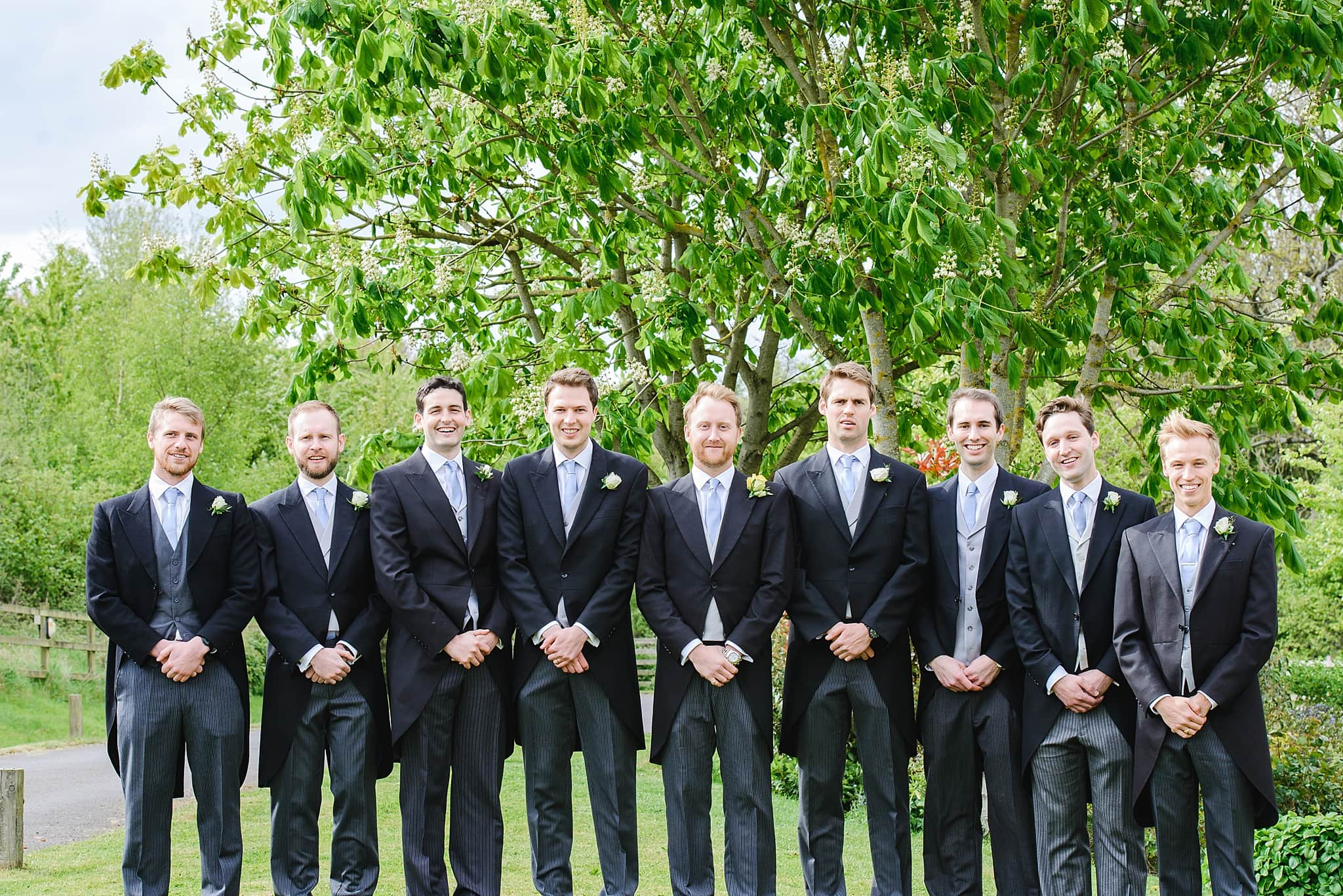 Groomsmen pose in the grand of Wick Farm wedding venue