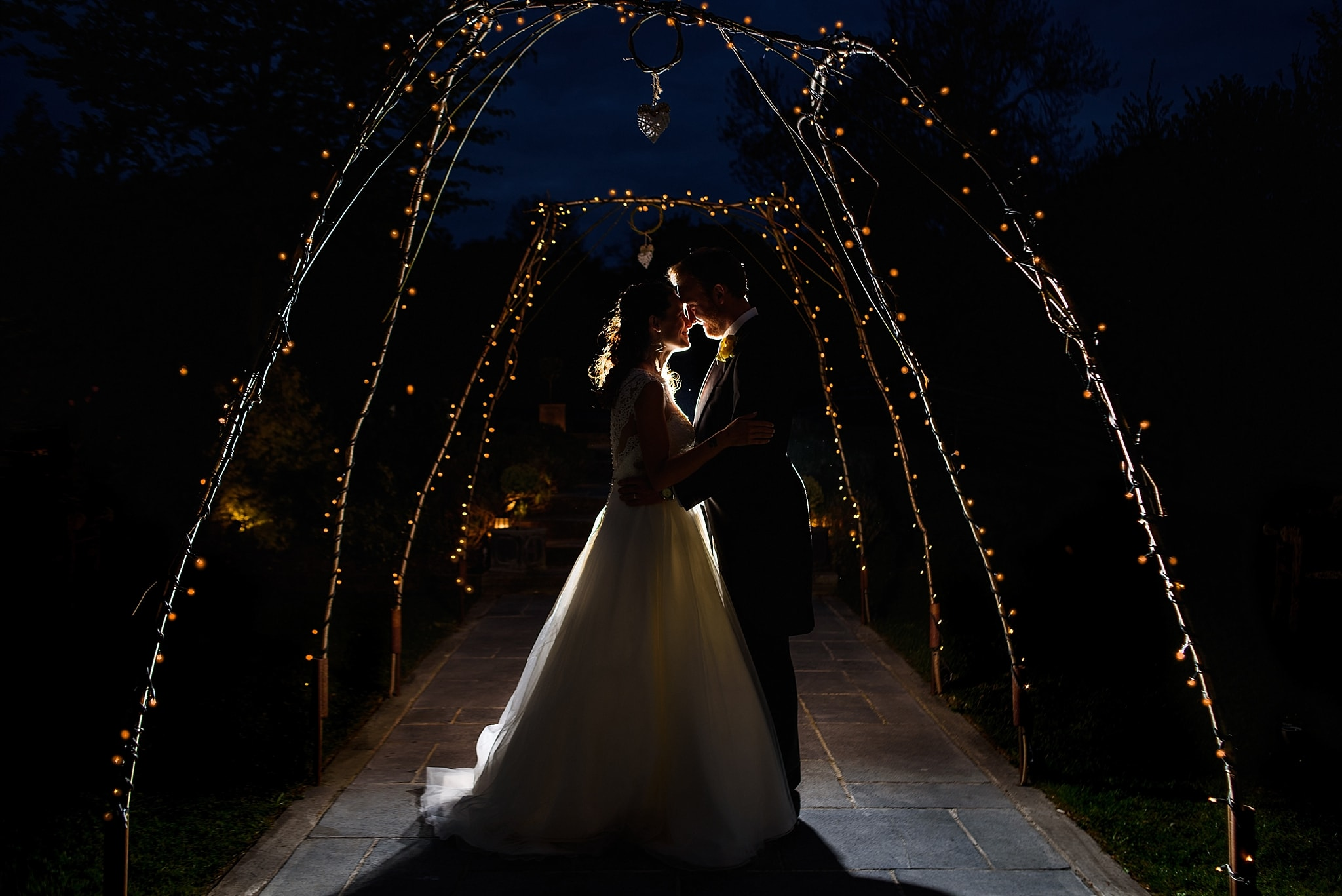 A night shot of bride and groom being back lit outside Wick Farm