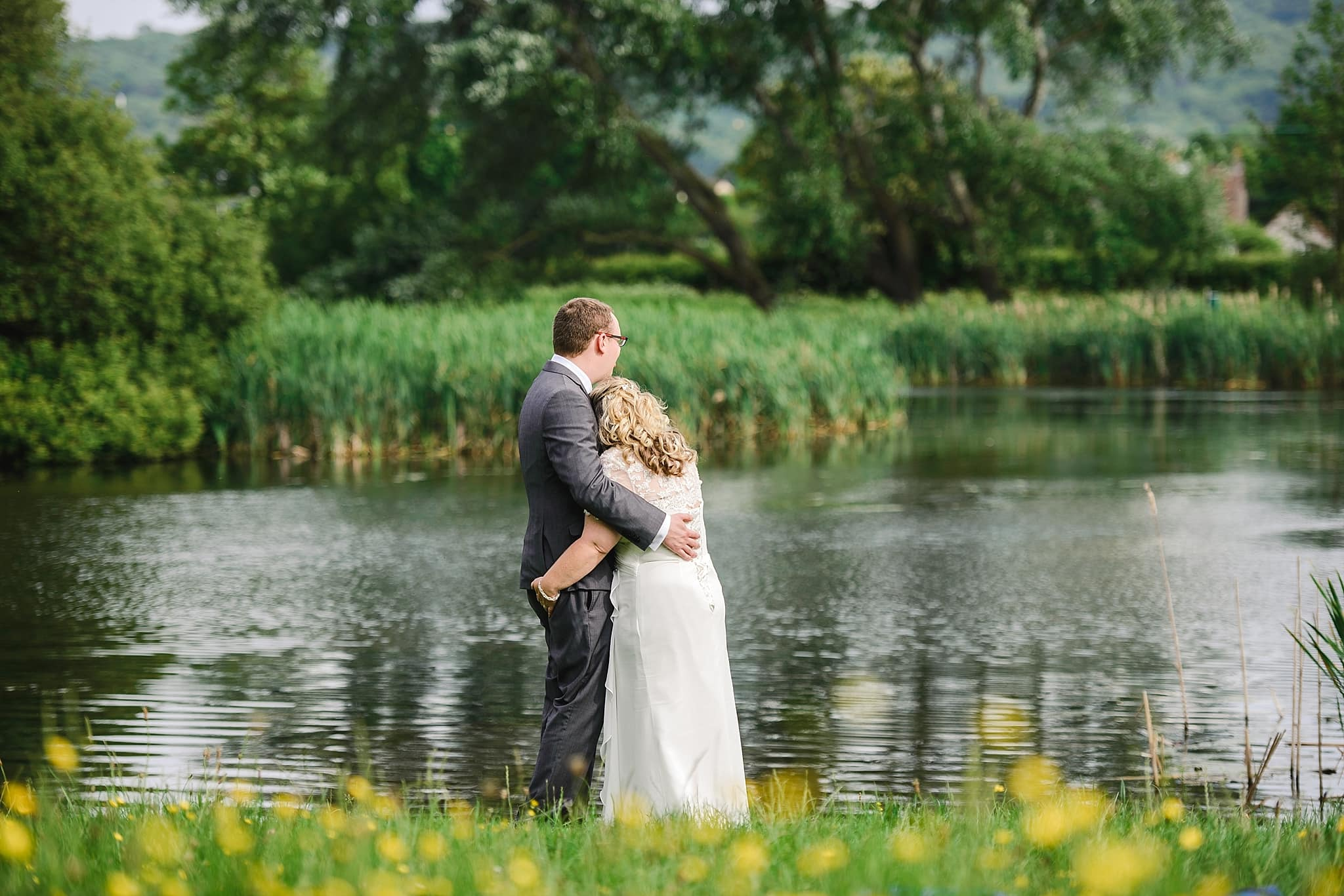 Couple look out on to the lake near their Nailsea Tithe barn wedding