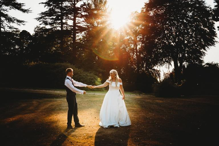 Bride and groom are dancing in the gardens of Coombe lodge at sunset